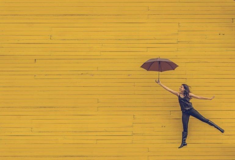 Mevrouw die zweeft aan de paraplu