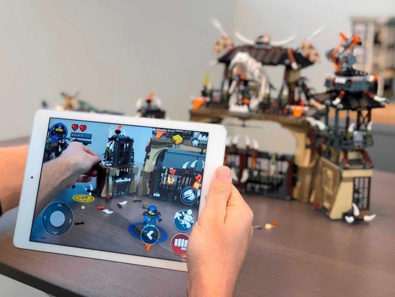 Quelqu'un tient un iPad avec l'application de terrain de jeu Lego ouverte.  Au moyen de la RA, la configuration Lego visible en arrière-plan sur l'iPad prend vie.