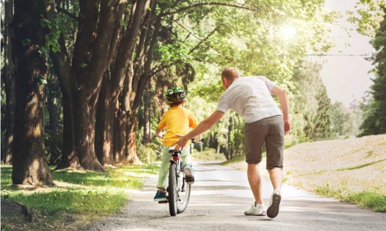 Kind leert fietsen.