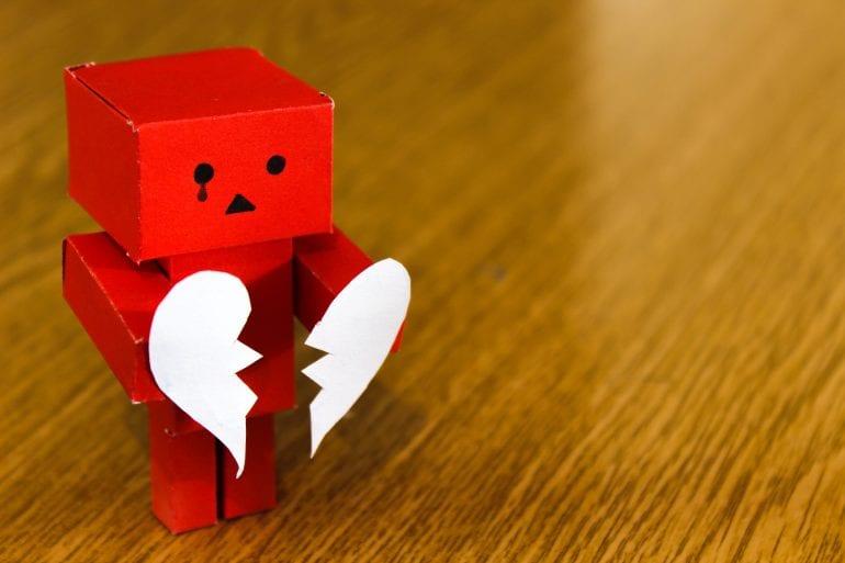 Een rood poppetje met een gebroken hart op tafel.