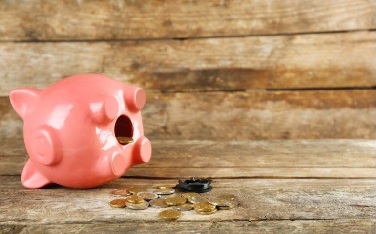 Spaarvarken op z'n kant met euromunten ernaast