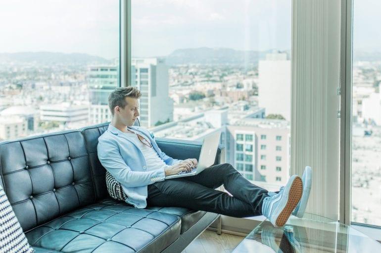 Foto van een persoon op de bank met een laptop op schoot, met uitzicht over de stad