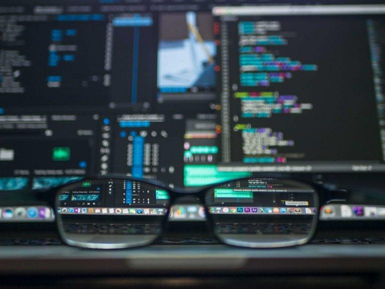Foto van een beeldscherm met daarvoor een bril; door de bril zijn verschillende app-pictogrammen uitvergroot