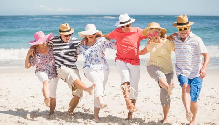 Oudere mensen die dansen op het strand, arm in arm