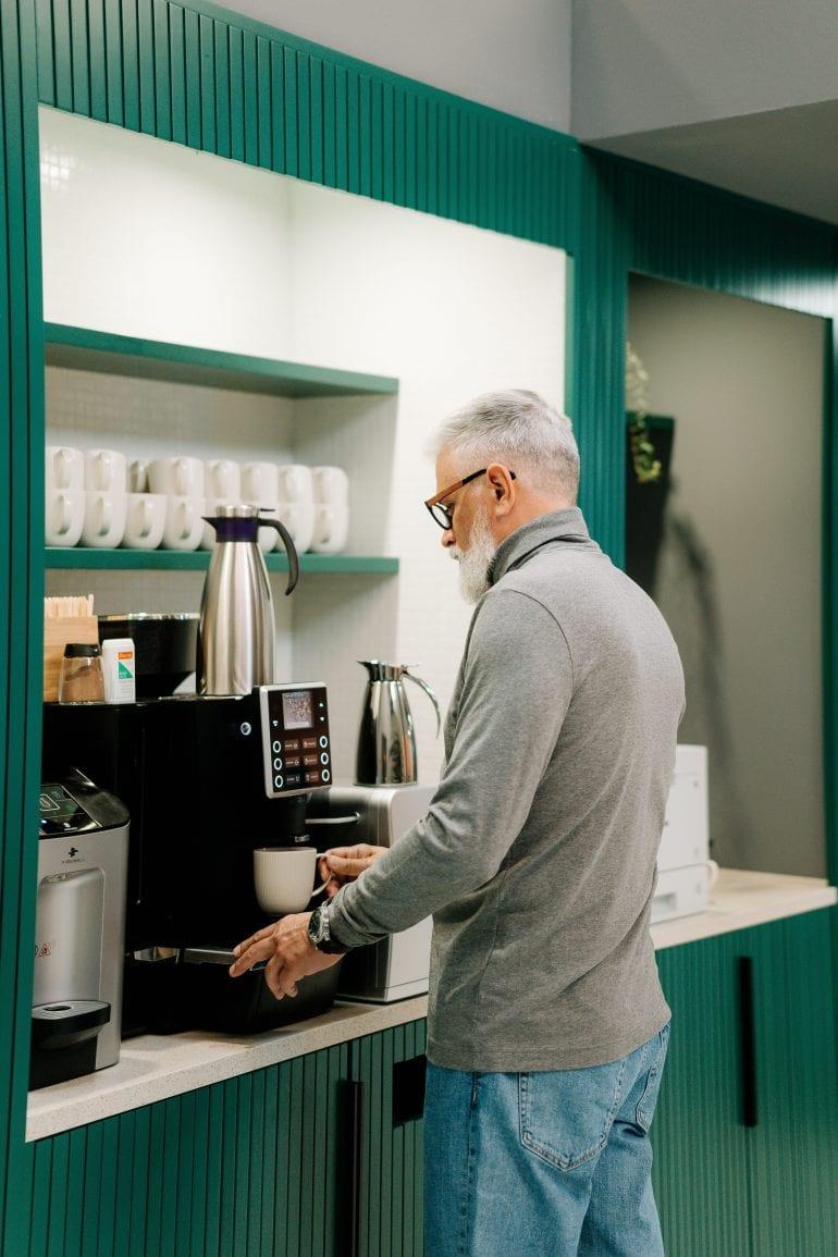 Foto van een man bij een koffieautomaat