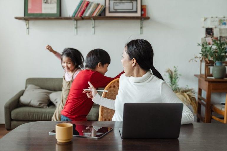 Foto van een vrouw met een laptop, met op de achtergrond spelende kinderen die de vrouw tot stilte maant