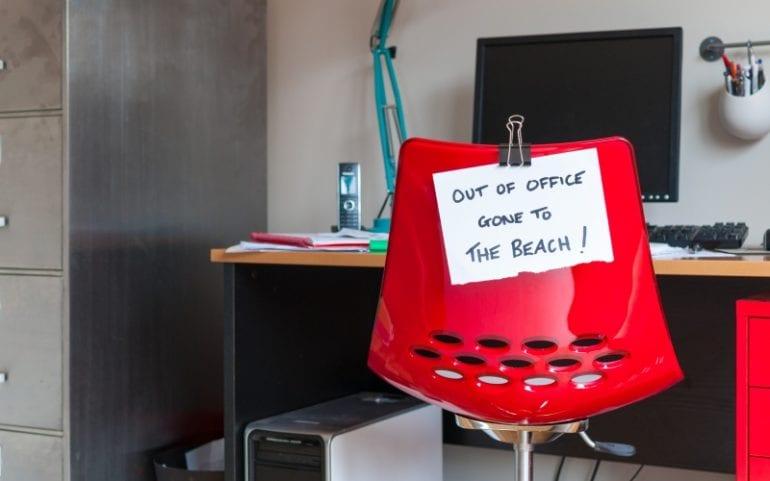 Bureau met briefje out of office en naar het strand