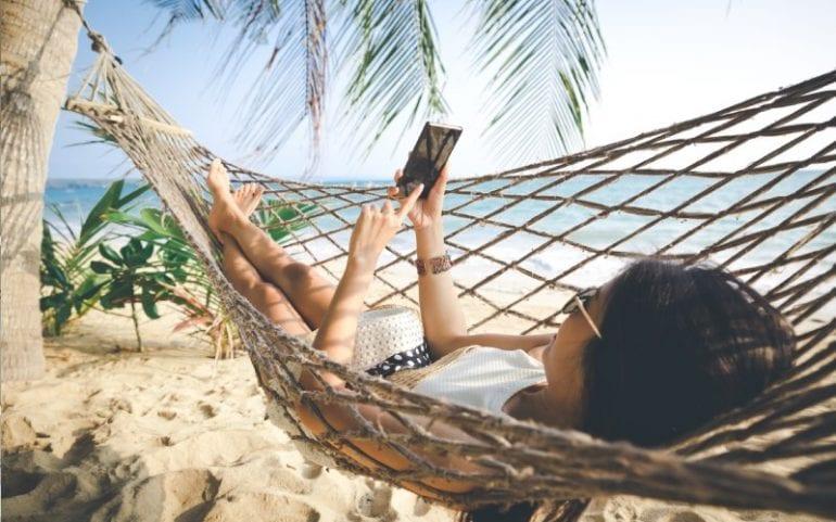 Vrouw in hangmat op strand kijkt op smartphone