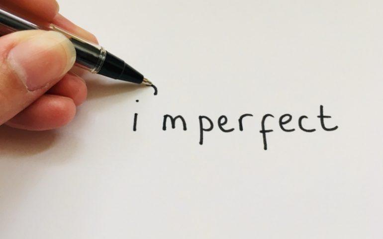 Hand met pen schrijft imperfect