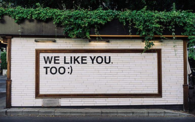 Muur met tekst we like you too bij social media update