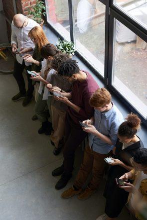 Foto de un grupo de personas que miran sus teléfonos inteligentes