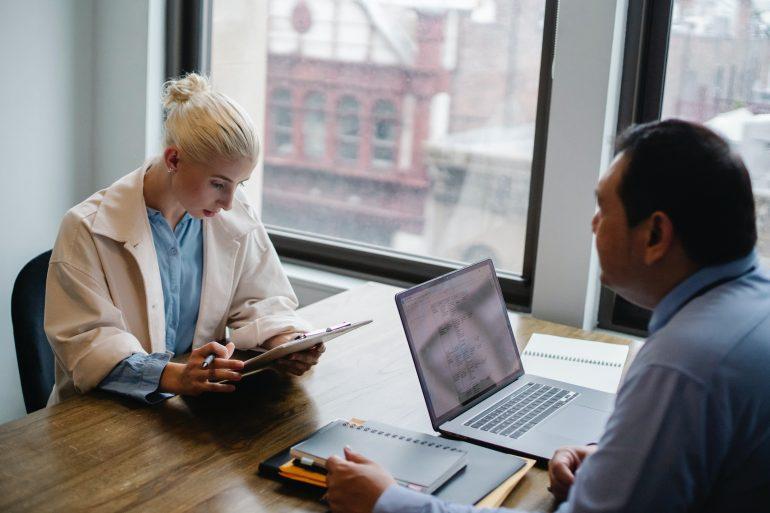 Foto de dos personas conversando, con una tableta o una computadora portátil frente a ellos