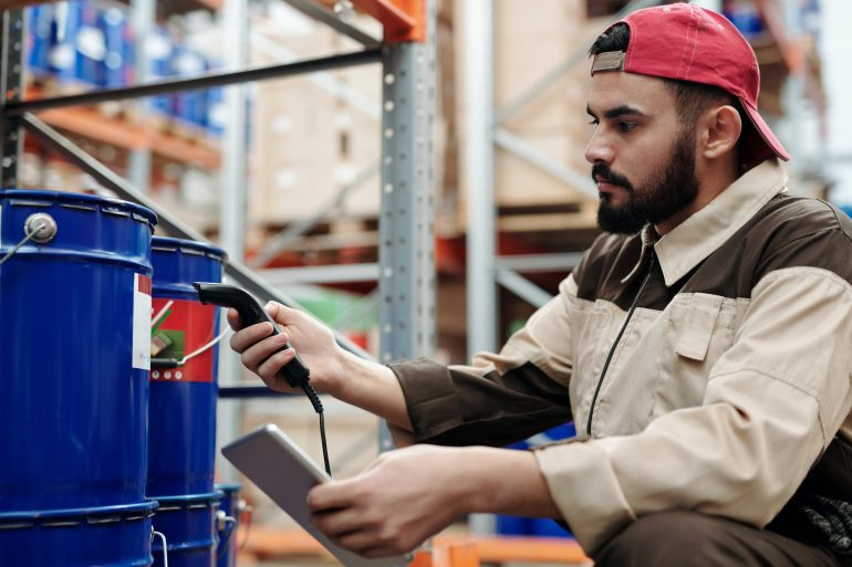 Foto de un hombre en ropa de trabajo con un escáner de mano