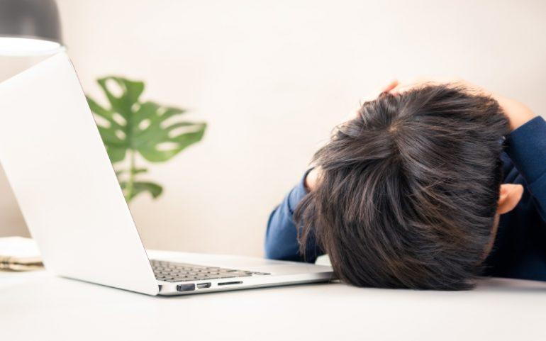 Kind met hoofd op tafel achter laptop ter illustratie van negatieve effecten social media op kinderen