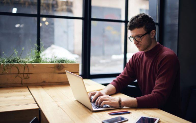 Man achter laptop bij artikel over duidelijke zakelijke teksten schrijven