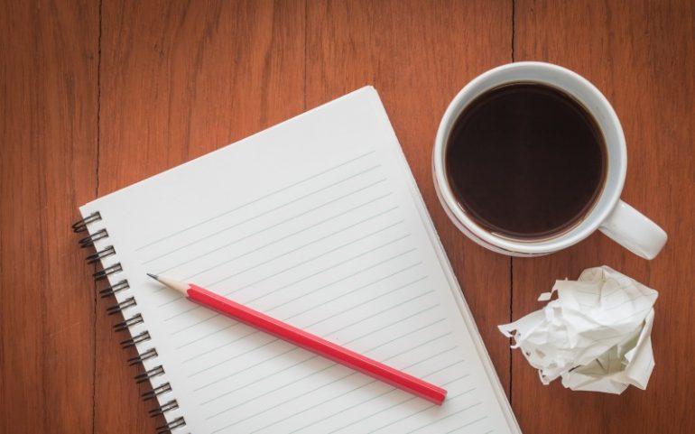 Notitieboek met potlood kop koffie en prop papier bij artikel over zakelijke duidelijke teksten schrijven